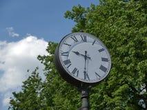 De oude klok in de straat in het Park met meningen van hemel en bomen Stock Afbeelding