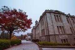 De oude klokketoren op het dak van het oude gebouw heeft rode bladeren, oranje en blauwe hemel De herfst in Yamagata, Japan, Wijn stock foto