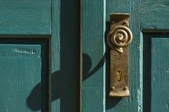 De oude knop van de messingsdeur met van een lus voorzien handvat op groene houten deur royalty-vrije stock foto