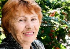De oude lachende vrouw op een achtergrond van aard Royalty-vrije Stock Afbeeldingen