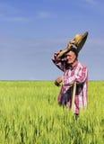 De oude landbouwer veegt het zweet op onderbreking van het werk op gebied af Royalty-vrije Stock Afbeelding