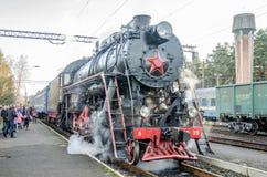 De oude locomotief van de ijzer zwarte retro uitstekende Sovjetstoom met rode ster komt bij het station aan om passagiers in clou Royalty-vrije Stock Afbeeldingen