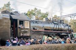 De oude locomotief van de ijzer zwarte retro uitstekende Sovjetstoom met rode ster komt bij het station aan om passagiers in de w Stock Fotografie