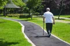 De oude man die in het park met een riet lopen stock fotografie