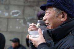 De oude man die yuanxiao eet royalty-vrije stock fotografie