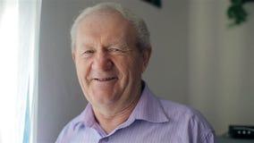 De oude man glimlacht bij de camera stock videobeelden