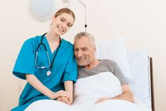 De oude man ligt op een wieg in de medische afdeling, en naast het is er een verpleegster royalty-vrije stock afbeeldingen