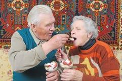 De oude man met de lepel voert oude vrouw Stock Foto