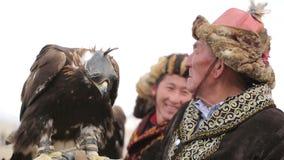 De oude man met gouden adelaar op de hand stock videobeelden