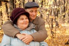 De oude man omhelst oude vrouw in herfstbos Stock Afbeelding