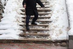 De oude man onderaan de treden glad in de winter stock afbeeldingen
