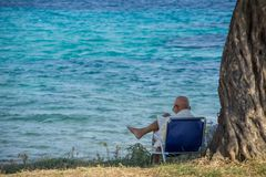 De oude man zit op een vouwende stoel naast een boom en leest het boek met zeewater op achtergrond royalty-vrije stock fotografie