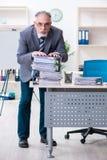 De oude mannelijke werknemer ongelukkig met het bovenmatige werk royalty-vrije stock afbeelding
