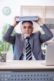 De oude mannelijke werknemer ongelukkig met het bovenmatige werk stock afbeeldingen