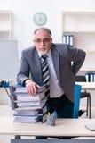 De oude mannelijke werknemer ongelukkig met het bovenmatige werk royalty-vrije stock afbeeldingen
