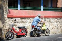 De oude mens begint motor van zijn motorfiets Royalty-vrije Stock Afbeeldingen