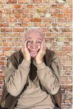 De oude mens behandelt zijn gezicht met zijn handen Royalty-vrije Stock Afbeeldingen