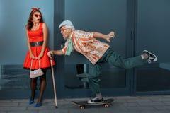 De oude mens berijdt snel een skateboard op de straat stock afbeelding