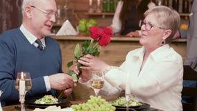 De oude mens biedt drie rode rozen aan zijn vrouw op een romantisch diner aan stock videobeelden