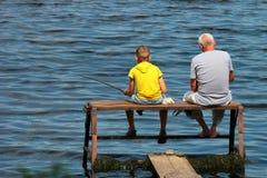 De oude mens en een jongen zitten op een zelf-gemaakt visserijplatform met staven stock foto