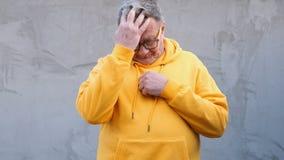 De oude mens in heldere kleren denkt over iets, en vindt dan een oplossing stock video