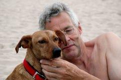 De oude mens loopt zijn hond stock foto's