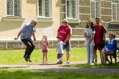 De oude mens springt kabel bij de amateurconcurrentie in de zomerdag stock afbeelding