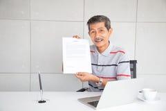 De oude mens toont contractdocument na teken en glimlach met gelukkig gevoel stock foto