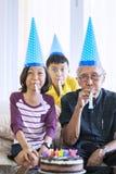 De oude mens viert verjaardag met kleinkinderen stock foto's