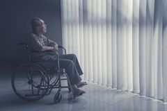 De oude mens zit op rolstoel terwijl het dagdromen royalty-vrije stock foto