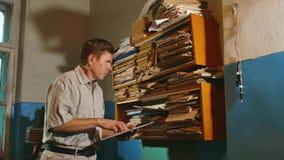 De oude mensenaccountant in een oud bureau onderzoekt document meldend de documenten oud zakenman professioneel werkend bureau stock videobeelden