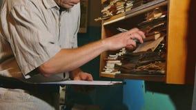 De oude mensenaccountant in een oud bureau onderzoekt document meldend de documenten oud zakenman professioneel werkend bureau stock footage