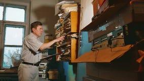 De oude mensenaccountant in een oud bureau onderzoekt document meldend de documenten oud zakenman professioneel werkend bureau stock video