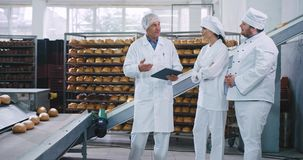 De oude menseningenieur heeft een praatje met twee bakkers in een bakkersbedrijf hij de nota's over de geautomatiseerde transport stock videobeelden