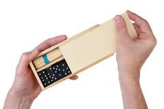De oude mensenopa opent een houten doos met raadsspelen - domino Royalty-vrije Stock Foto's