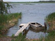 De oude metaalboot is gebonden bij een houten pijler overziend de rivier stock afbeelding