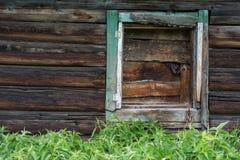 De oude muur van logboeken met ingescheept op venster Stock Afbeeldingen