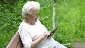 De oude oma bekijkt Internet-smartphone stock footage