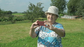 De oude oma neemt foto's de aard van park stock footage