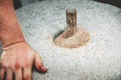 De oude quern molen van de steenhand met korrel dichte omhooggaand De man maalt de korrel in bloem met behulp van een molensteen stock afbeelding