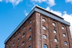 De oude rode baksteenbouw of fabriek met vele kleine vensters Stock Afbeelding