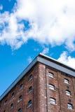 De oude rode baksteenbouw of fabriek met vele kleine vensters Stock Afbeeldingen