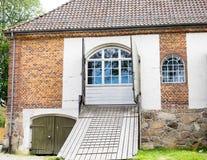 De oude rode baksteenbouw met houten brugweg Stock Foto's