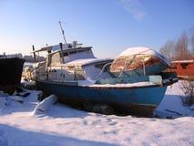 De oude roestige die boot aan de kust in de winter wordt vastgelegd bevroor op de rivier stock afbeelding