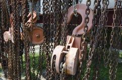 De oude roestige ketting en de katrol van het metaalhijstoestel Stock Fotografie