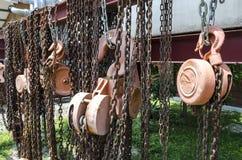 De oude roestige ketting en de katrol van het metaalhijstoestel Stock Afbeeldingen