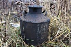 De oude roestige Sovjetmelk kan in het gras royalty-vrije stock afbeeldingen
