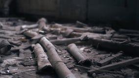 De oude rotte pijpen zijn in een verlaten gebouw, onder het huisvuil stock video