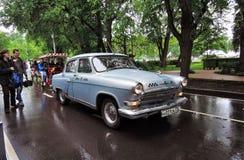 De oude Russische aandrijving van de taxiauto op de natte weg Stock Foto