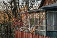De oude rustieke ingang van de huisveranda aan uitstekend huis met rood hout royalty-vrije stock afbeelding